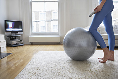 A woman completing fitness exercises in her home that she learned from training at Phoenix Athletica in Pocono Summit, PA